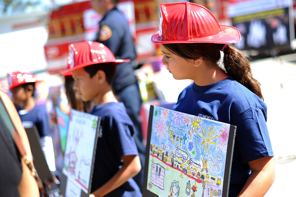 . Students display their award winning artwork depicting a safe 4th of July during an LAFD news conference regarding the use of fireworks as the 4th of July holiday approaches.  Fire and law enforcement officials are encouraging families to attend a professional fireworks show to reduce fires and injuries.(Andy Holzman/Los Angeles Daily News)