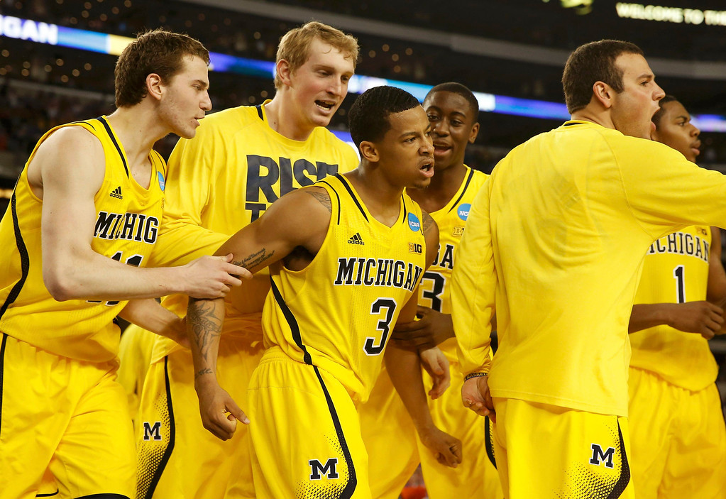 . Michigan Wolverines guard Trey Burke (3) celebrates with teammates after shooting a three point basket to tie the game against the Kansas Jayhawks during the second half in their South Regional NCAA men\'s basketball game in Arlington, Texas March 29, 2013. REUTERS/Jim Young