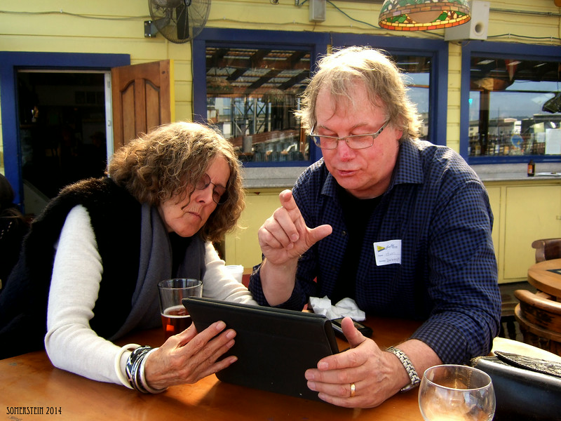 Eva Strauss-Rosen (artist), left and Jim English (CEO-nutrition company) looking at Eva's iPad - Mark Rennie and his friend Michelle's birthday party at Bayview Boat Club