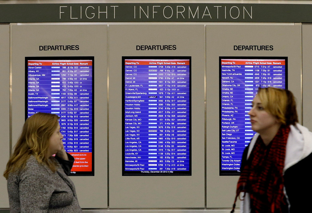 . A flight information screen displays canceled flights as passenger walk at Midway airport in Chicago, Thursday, Dec. 20, 2012. The first widespread snowstorm of the season crawled across the Midwest on Thursday, with whiteout conditions stranding holiday travelers. The storm led airlines to cancel about 1,000 flights ahead of the Christmas holiday ó relatively few compared to past big storms, though the number was climbing.  Southwest Airlines scratched all of its flights scheduled after 4:30 p.m. today at Midway. (AP Photo/Nam Y. Huh)