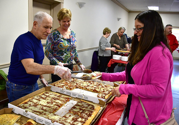 3/14/2019 Mike Orazzi | Staff\rSal Mangiafico serves pizza to Beth Neumann as Nancy Kaczynski looks on during the Plainville Chamber of Commerce  2019 Pizza Feud at the Veterans of Foreign Wars in Plainville Thursday evening.