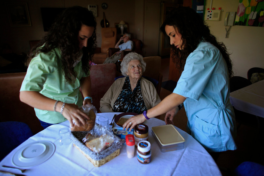 . Spanish nurses Maria Jose Marin (R), 23, and her twin sister Maria Teresa prepare food for a woman in the Deo Gratias nursing home in The Hague, June 7, 2013. After months of studying Dutch, a group of young Spanish nurses moved to the Netherlands to take up work, fleeing a dismal job market at home. Spain\'s population dropped last year for the first time on record as young professionals and immigrants who moved here during a construction boom head for greener pastures. Spain\'s jobless rate is 27 percent, and more than half of young workers are unemployed. For Spanish nurses, the Netherlands\' nursing deficit is a boon. Picture taken June 7, 2013.  REUTERS/Marcelo del Pozo