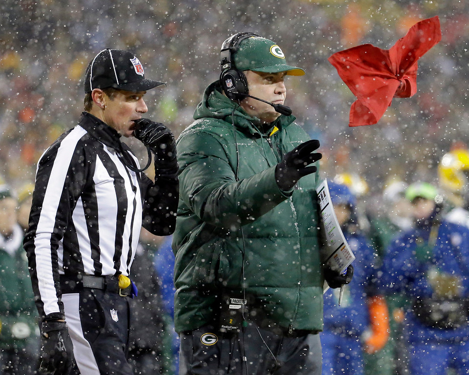 . Head linesman Kent Payne (79) watches as Green Bay Packers head coach Mike McCarthythrows his challenge flag during the second half of an NFL football game against the Pittsburgh Steelers Sunday, Dec. 22, 2013, in Green Bay, Wis. The play was reversed and the Packers were credited with a fumble recovery. (AP Photo/Morry Gash)