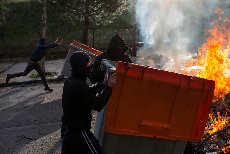 . Students push containers to add them to the fire, started by students, during the first day of a student strike to protest a government education reform and cutbacks in grants and staffing, at Complutense University in Madrid, Spain, Wednesday, March 26, 2014. Spanish police say they\'ve arrested more than 50 students when the police moved in to end the occupation of a campus building after the university had asked them to intervene. Students, many with their faces covered, set fire to trash containers and set up barricades on at least two streets in the university complex during the protest. (AP Photo/Andres Kudacki)