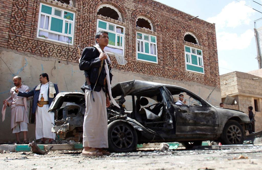 . Houthi fighters stand near a damaged car after suicide attack in Sanaa, Yemen, Friday, March 20, 2015. Triple suicide bombers hit a pair of mosques crowded with worshippers in the Yemeni capital, Sanaa, on Friday, causing heavy casualties, according to witnesses. The attackers targeted mosques frequented by Shiite rebels, who have controlled the capital since September. (AP Photo/Hani Mohammed)