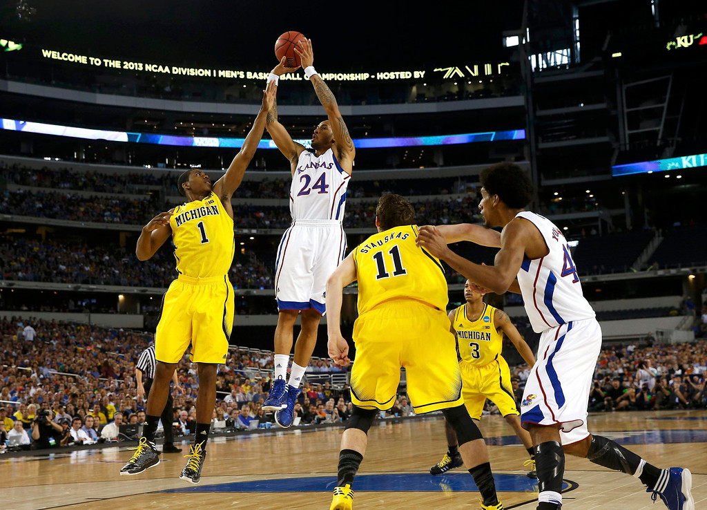 . Kansas Jayhawks guard Travis Releford (24) shoots over Michigan Wolverines forward Glenn Robinson III during the first half in their South Regional NCAA mens basketball game in Arlington, Texas March 29, 2013. REUTERS/Jim Young