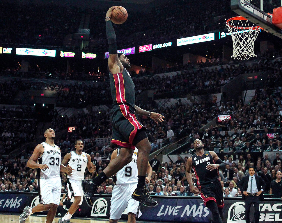 . Miami Heat forward LeBron James, center, dunks against San Antonio forward Boris Diaw (33), forward Kawhi Leonard and guard Tony Parker (9), of France, during the second quarter of Game 5 in the NBA Finals basketball series in San Antonio on Sunday, June 16, 2013. (AP Photo/El Nuevo Herald, David Santiago )  MAGS OUT