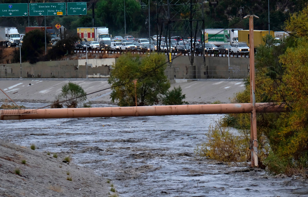 . Northbound traffic comes to a standstill on Interstate 5 freeway near the rushing water filled Los Angeles river near downtown Los Angeles on Tuesday, Dec. 9, 2018. The first significant storm of the season walloped much of California with damaging winds and thunderstorms. (AP Photo/Richard Vogel)