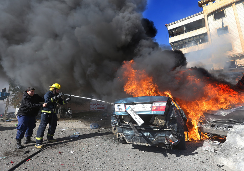 . Lebanese firefighters extinguish a burned car at the site of an explosion, in the suburb of Beir Hassan, Beirut, Lebanon, Wednesday Feb. 19, 2014.  (AP Photo/Hussein Malla)