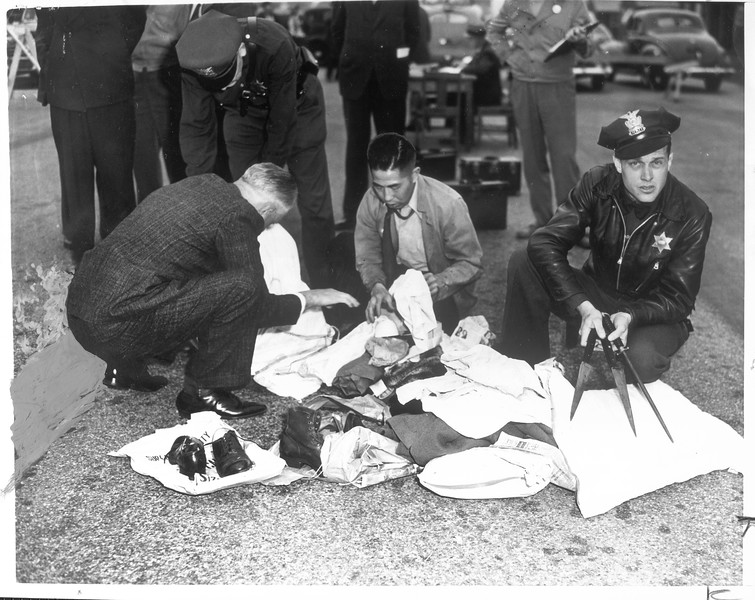 """""""Alarm spread yesterday when officers examining evacuees' baggage discovered knives wrapped in belongings of Kisuki Okasaki"""" -- caption on photograph"""