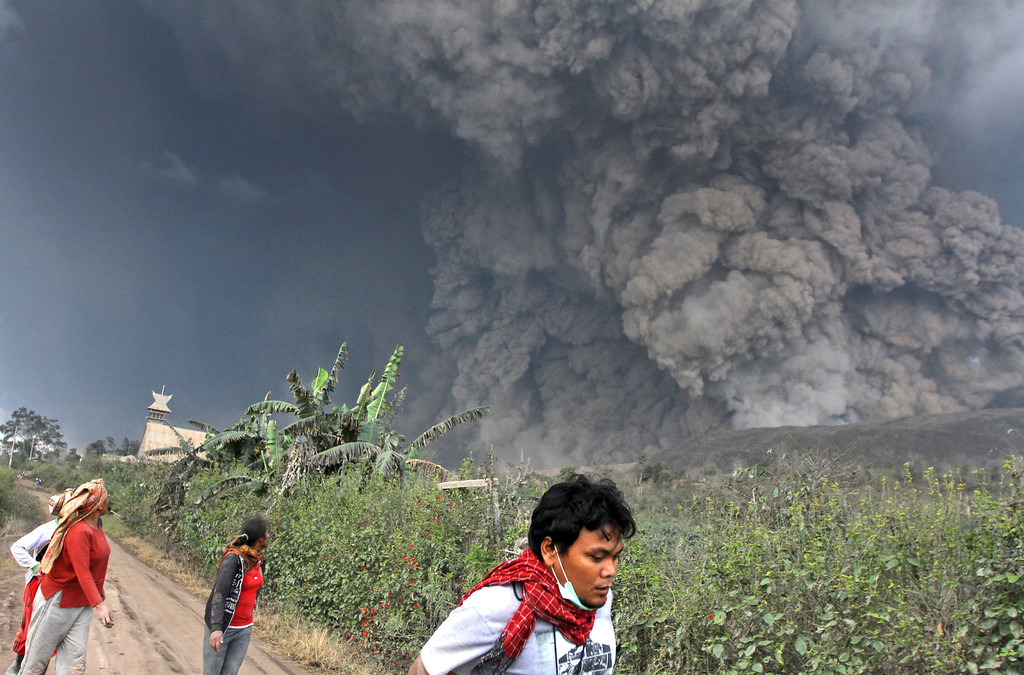 . Villagers and a journalist prepare to flee as Mount Sinabung releases pyroclastic flows during an eruption in Namantaran, North Sumatra, Indonesia, Saturday, Feb. 1, 2014. The rumbling volcano in western Indonesia has unleashed fresh clouds of searing gas, killing a number people and injuring fewothers. (AP Photo)