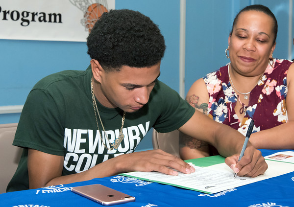 05/25/18 Wesley Bunnell | Staff Basketball standout at E.C. Goodwin High School Francisco Santiago II signed his papers intending to attend and play basketball for Newbury College as his mother Marsha Michaud looks on. The signing took place at St. Matthew's on Friday night.