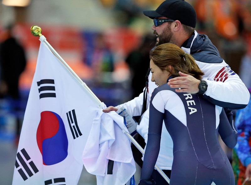 . A coach hugs Gold medalist South Korea\'s Lee Sang-hwa after she set a new Olympic record for the women\'s 500-meter speed skating at the Adler Arena Skating Center during the 2014 Winter Olympics, Tuesday, Feb. 11, 2014, in Sochi, Russia. (AP Photo/Matt Dunham)
