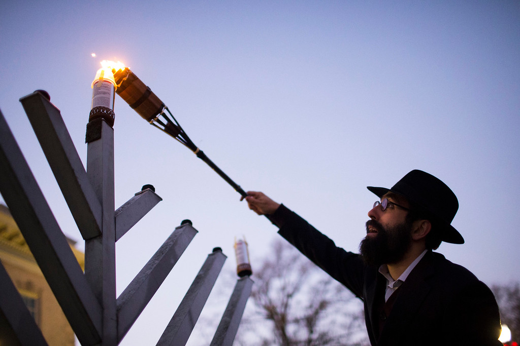 . Rabbi Michoel Refson, of Athens, lights the Menorah to celebrate the first day of Hanukkah in front of City Hall in downtown Athens, Ga. Tuesday, Dec. 12, 2017. (Joshua L. Jones/Athens Banner-Herald via AP)