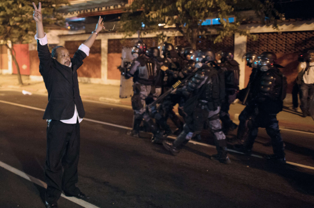 . A demonstrator flashes the victory sign as military police from the special unit Choque advance late on June 19, 2013 during clashes in the center of Niteroi, 10 kms from Rio de Janeiro. Protesters battled police late on June 19, even after Brazil\'s two biggest cities rolled back the transit fare hikes that triggered two weeks of nationwide protests.  The fare rollback in Sao Paulo and Rio de Janeiro marked a major victory for the protests, which are the biggest Brazil has seen in two decades. CHRISTOPHE SIMON/AFP/Getty Images
