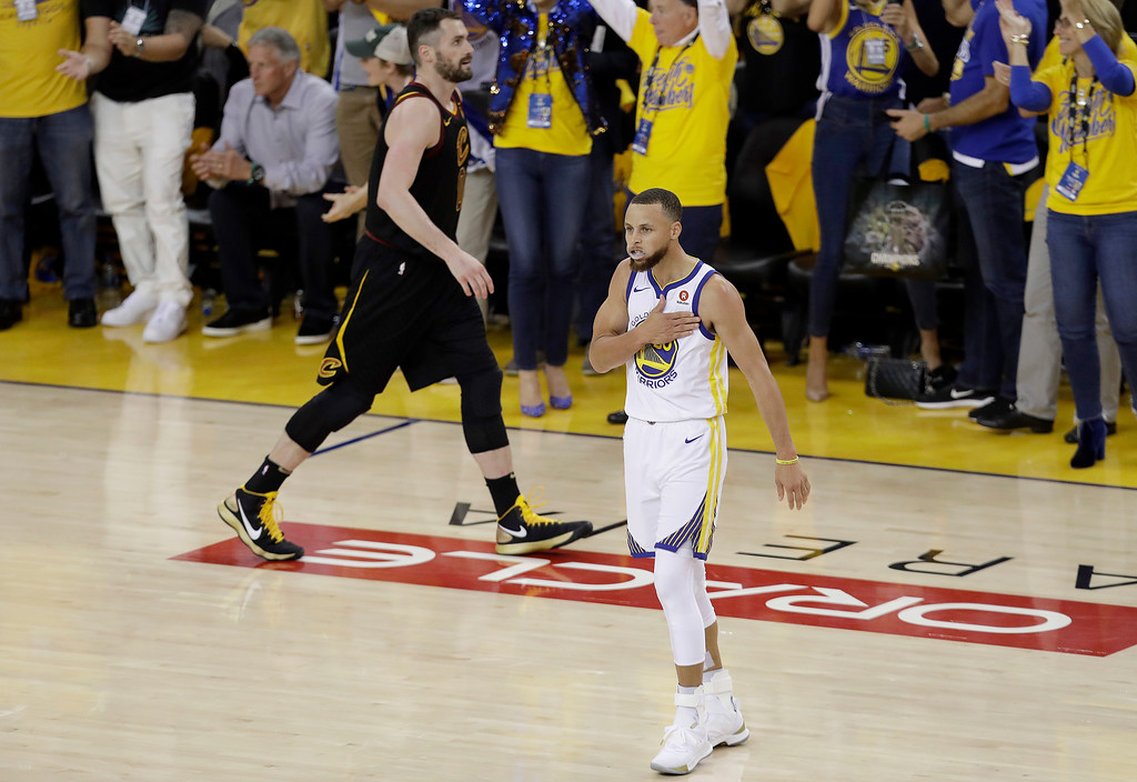 . Golden State Warriors guard Stephen Curry (30) celebrates in front of Cleveland Cavaliers forward Kevin Love during overtime of Game 1 of basketball\'s NBA Finals in Oakland, Calif., Thursday, May 31, 2018. (AP Photo/Marcio Jose Sanchez)