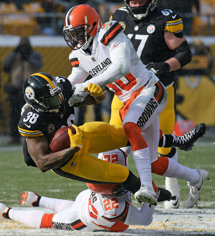 . Pittsburgh Steelers running back Stevan Ridley (38) is tackled by Cleveland Browns free safety Jabrill Peppers (22) and cornerback Jason McCourty (30) during the first half of an NFL football game in Pittsburgh, Sunday, Dec. 31, 2017. (AP Photo/Don Wright)