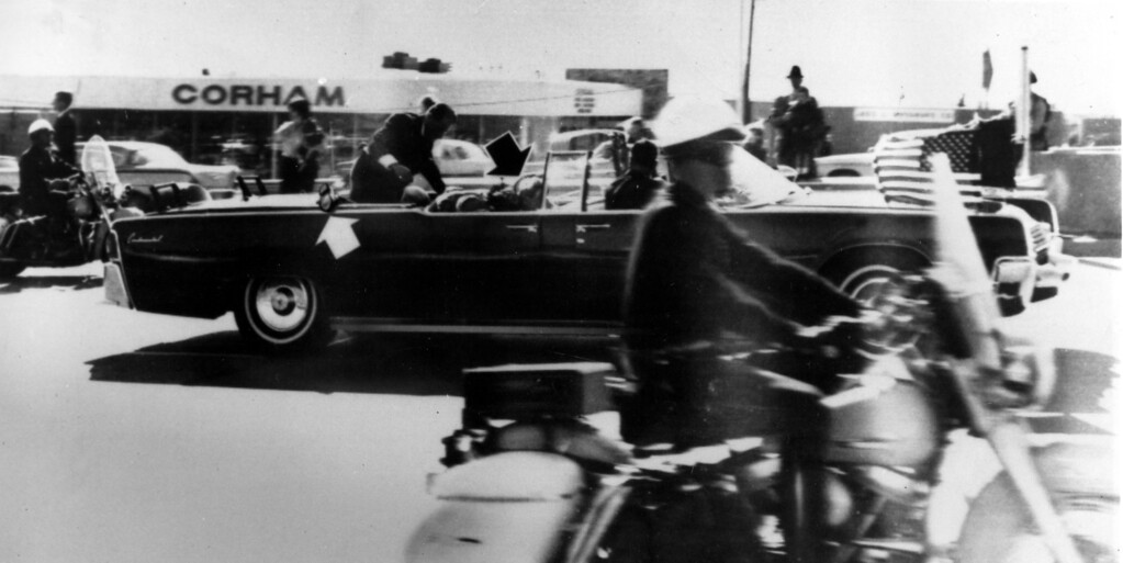 . Secret Service agent Clint Hill climbs into the back seat of the limousine a moment after President John F. Kennedy and Governor John Connally of Texas were shot in Dallas, Nov. 22, 1963.  Black arrow points to Mrs. Connally ducking bullets, and white arrow points out the agent\'s foot, mistakenly thought to be the president\'s when the photo first ran.  (AP Photo)