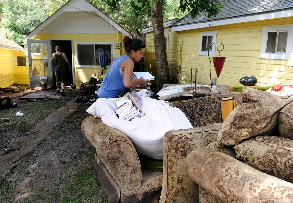 . MANITOU SPRINGS, CO - Aug.10: Kiandra Pfaffl and her mother Tammy rent the house behind her and watched as floodwaters washed away the house behind directly theirs. Pfaffl piles books on her couch as she joins residents and crews clean up the damage and debris along Canon Avenue after a flash flood roared through the streets and hillsides on Friday evening. (Photo By Kathryn Scott Osler/The Denver Post)