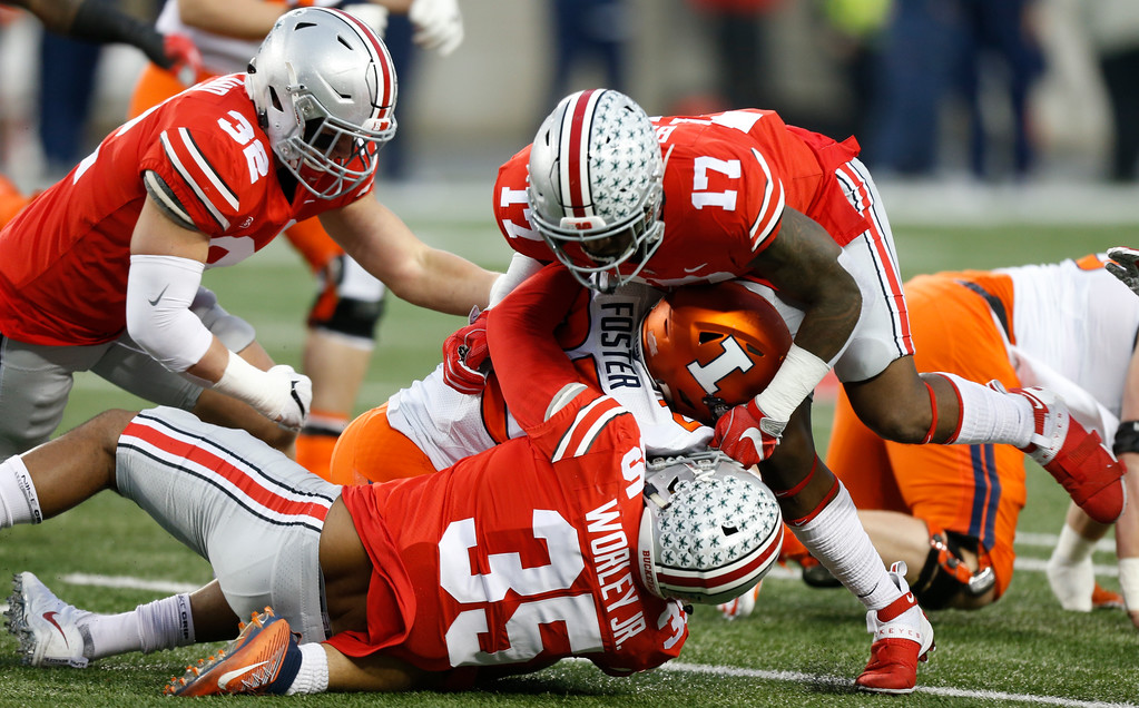 . Ohio State linebackers Tuf Borland, left, Jerome Baker, top, and Chris Worley, bottom, tackle Illinois running back Kendrick Foster during the first half of an NCAA college football game Saturday, Nov. 18, 2017, in Columbus, Ohio. (AP Photo/Jay LaPrete)