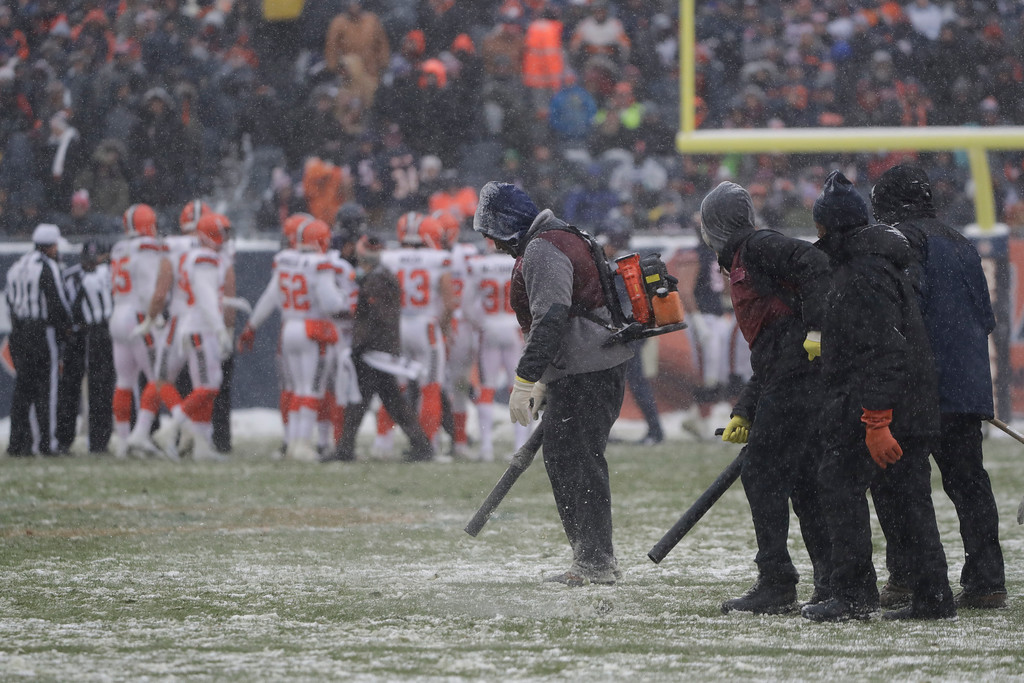 . Workers clear snow from the field during an NFL football game between the Chicago Bears and Cleveland Browns in Chicago, Sunday, Dec. 24, 2017. (AP Photo/Nam Y. Huh)