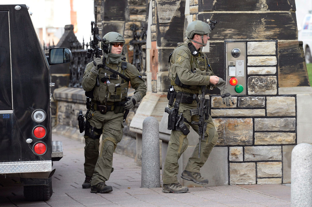 . A Royal Canadian Mounted Police intervention team walks past a gate on Parliament hill in Ottawa Wednesday Oct. 22, 2014. A soldier standing guard at the National War Memorial has been shot by an unknown gunman and there have been reports of gunfire inside the halls of Parliament. Emergency responders are still on the scene as paramedics performed CPR on the soldier before he was taken away by ambulance.  (AP Photo/The Canadian Press, Adrian Wyld)