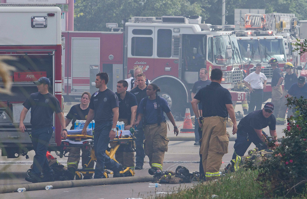 . Firefighters bring drinking water on a stretcher at the scene of a five-alarm fire where four firefighters were killed battling the blaze at a restaurant and hotel in southwest Houston May 31, 2013.     REUTERS/Richard Carson