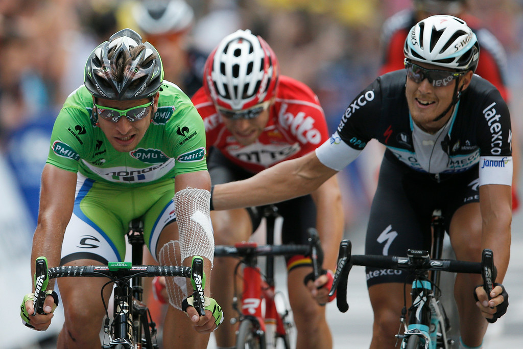 . Stage winner Matteo Trentin of Italy taps second place Peter Sagan of Slovakia on the back as he crosses the finish line to win the seventh stage of the Tour de France cycling race over 234.5 kilometers (145.7 miles) with start in Epernay and finish in Nancy, France, Friday, July 11, 2014. (AP Photo/Peter Dejong)