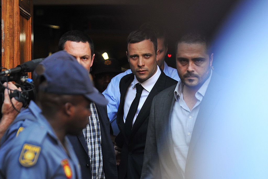 """. South African Paralympic athlete Oscar Pistorius (C) leaves the High Court in Pretoria on September 11, 2014, after receiving the verdict in his murder trial. \""""Blade Runner\"""" Oscar Pistorius was found not guilty of murdering his girlfriend Reeva Steenkamp on September 11, 2014, a shock decision that left the South African celebrity athlete sobbing with emotion in the dock. The high-profile trial was adjourned until the next day when the 27-year-old Paralympian will hear whether he has been found guilty of culpable homicide, a lesser charge roughly equivalent to manslaughter. GIANLUIGI GUERCIAGIANLUIGI GUERCIA/AFP/Getty Images"""