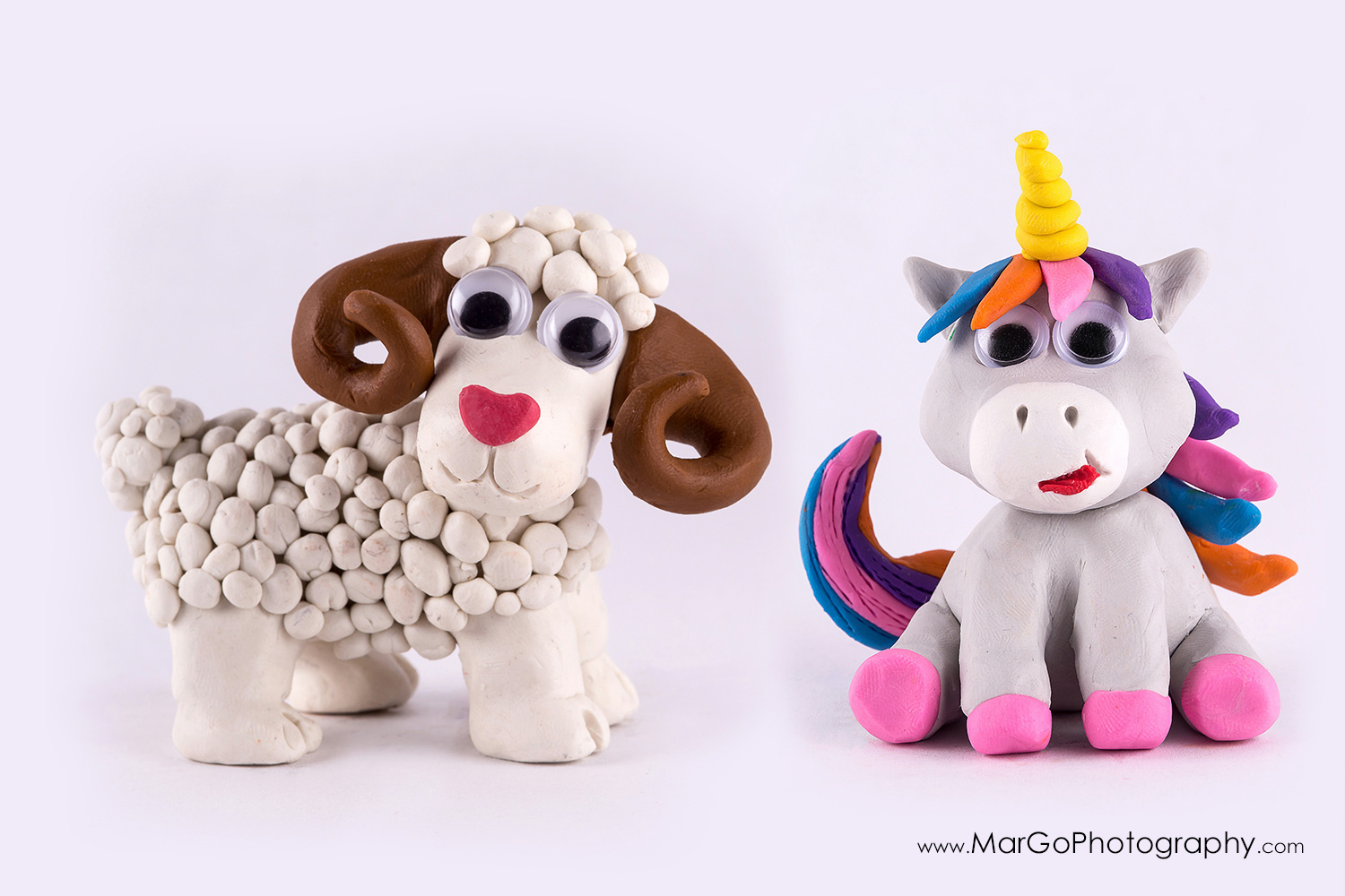 photography of clay white ram and colorful unicorn on white background