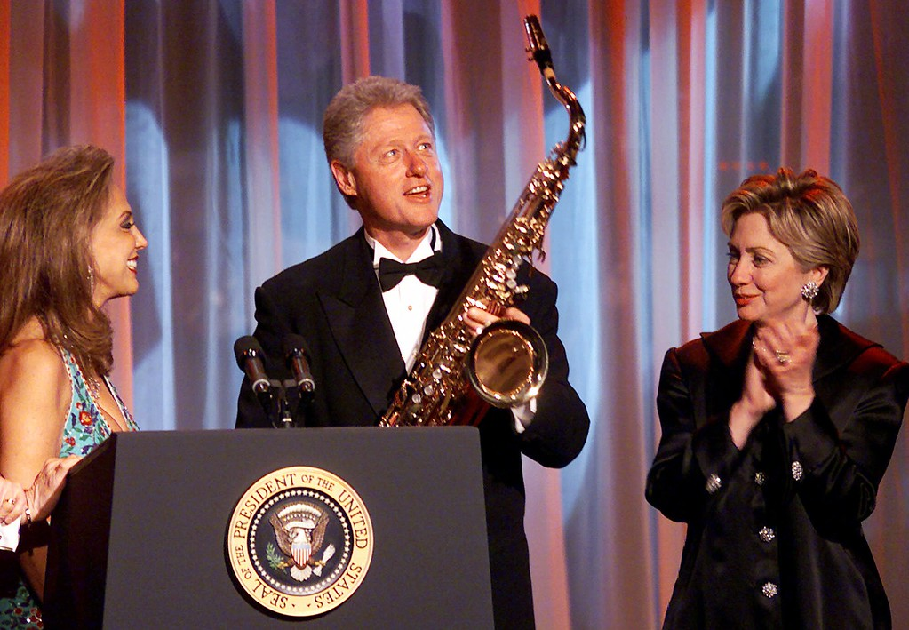. President Clinton accepts a saxophone from Denise Rich as Senator-elect Hillary Rodham Clinton D-N.Y. applauds at the G&P Foundation Angel Ball 2000 dinner at the New York Marriott Marquis Hotel in New York, Thursday, Nov. 30, 2000, in New York. Rich is a co-founder of the foundation. (AP Photo/Mark Lennihan)