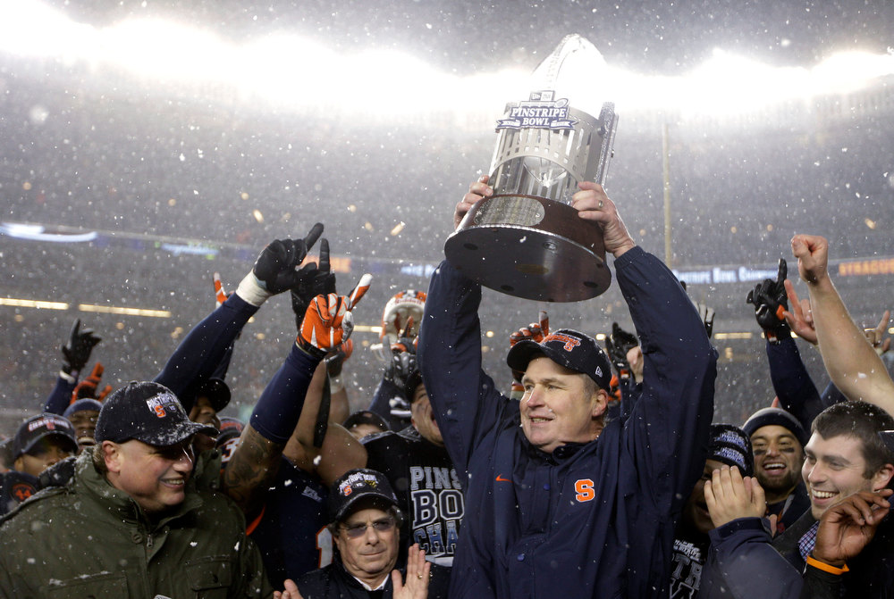 . New York Yankees president Randy Levine, left, and chief operating officer Lonn Trost, center left, react after presenting the Pinstripe Bowl trophy to Syracuse coach Doug Marone after Syracuse defeated West Virginia 38-14 in the Pinstripe Bowl NCAA college football game at Yankee Stadium in New York, Saturday, Dec. 29, 2012. (AP Photo/Kathy Willens)