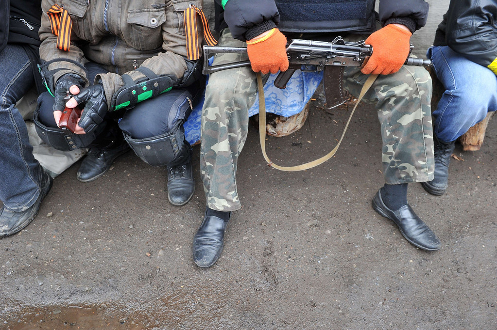 """. Armed pro-Russian protesters guard the regional police building seized by armed separatists in Slavyansk on April 13, 2014. Kiev said on April 13 that several had been left \""""dead and wounded\"""" in fighting to oust pro-Russian gunmen holed up in a police station in the restive eastern city of Slavyansk, as Washington warned Moscow to de-escalate the crisis or face the consequences. AFP PHOTO / GENYA SAVILOV"""