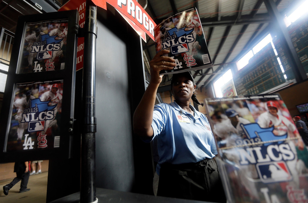 . Donna Hollingsworth sells programs before Game 2 of the National League baseball championship series between the St. Louis Cardinals and the Los Angeles Dodgers Saturday, Oct. 12, 2013, in St. Louis. (AP Photo/Jeff Roberson)