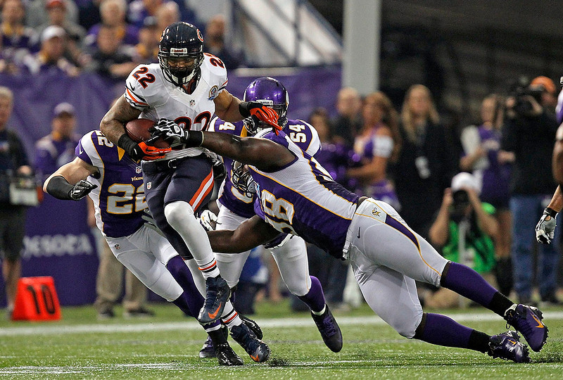 . Chicago Bears running back Matt Forte (22) is slowed down by Minnesota Vikings tackle Letroy Guion (98) during the first half of their NFL football game in Minneapolis, December 9, 2012. REUTERS/Eric Miller