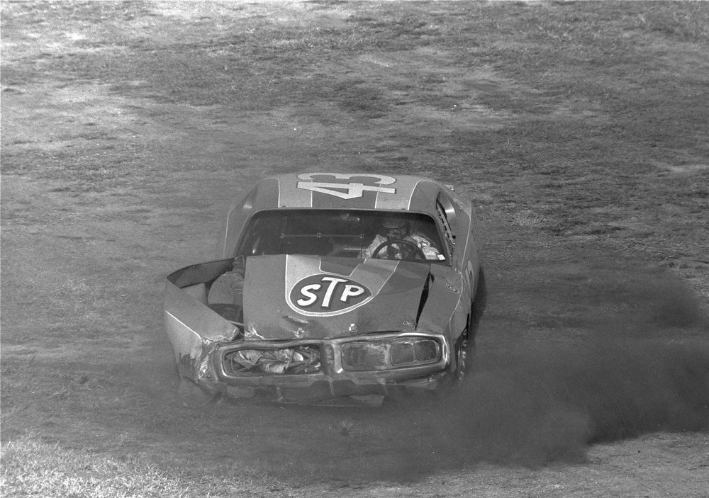Description of . Richard Petty of Randleman, N.C., car 43, tries to drive his car at the Daytona 500 at the Speedway, but had to be pushed over the finish line.  Petty crashed into David Pearson's car, then hit the wall on the final lap of the race on February 15, 1976.  (AP Photo)