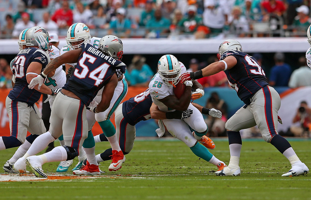 . Lamar Miller #26 of the Miami Dolphins rushes during a game against the New England Patriots at Sun Life Stadium on December 15, 2013 in Miami Gardens, Florida.  (Photo by Mike Ehrmann/Getty Images)