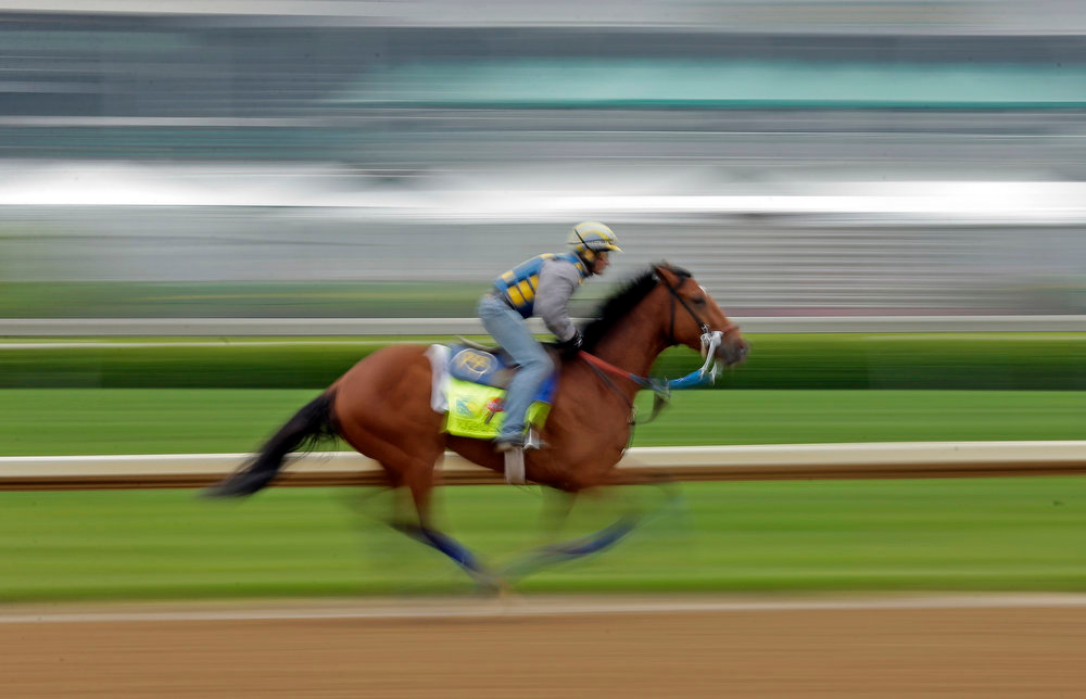 . Trainer Rudy Rodriguez rides Kentucky Derby entrant Vyjack for a workout at Churchill Downs Monday, April 29, 2013, in Louisville, Ky. (AP Photo/Charlie Riedel)