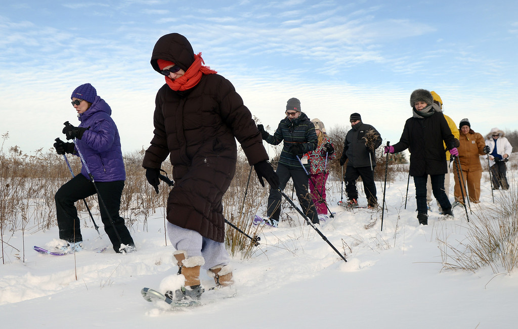 . Take a buddy and an emergency kit when you are participating in outdoor recreation. Pictured here, Debbie Meeks of Chardon, center, and Heather Kilfoyle of Munson Township, left, lead a group of snowshoers during a Learn to Snowshoe hike in January 2015 at Geauga Park District\'s Orchard Hills Park in Chester Township. (News-Herald file)