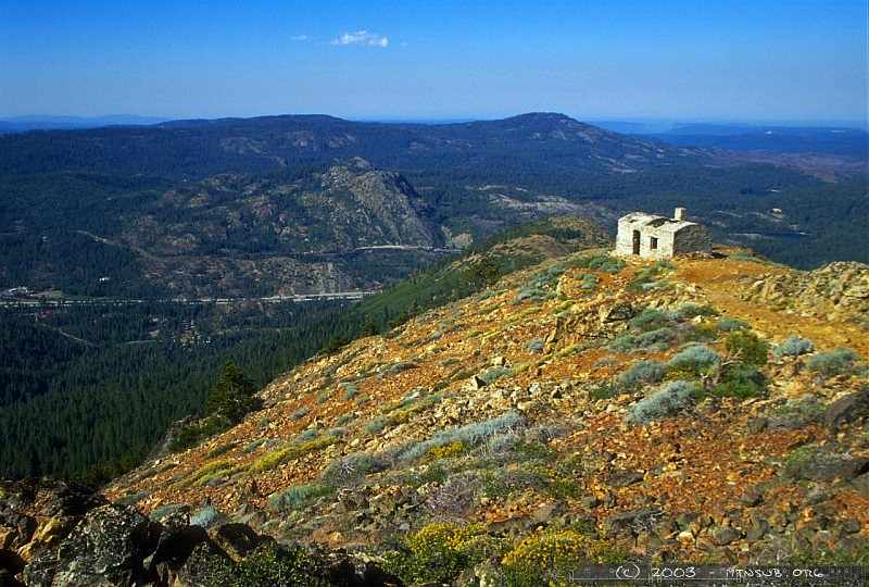 From the summit of Red Mountain, a view of SP's fire lookout shows the interstate and railroad deep down in the valley. This lookout was used to spot fires in the wooden snowsheds in the days of steam. Cisco and Butte Canon are visible in the distance.