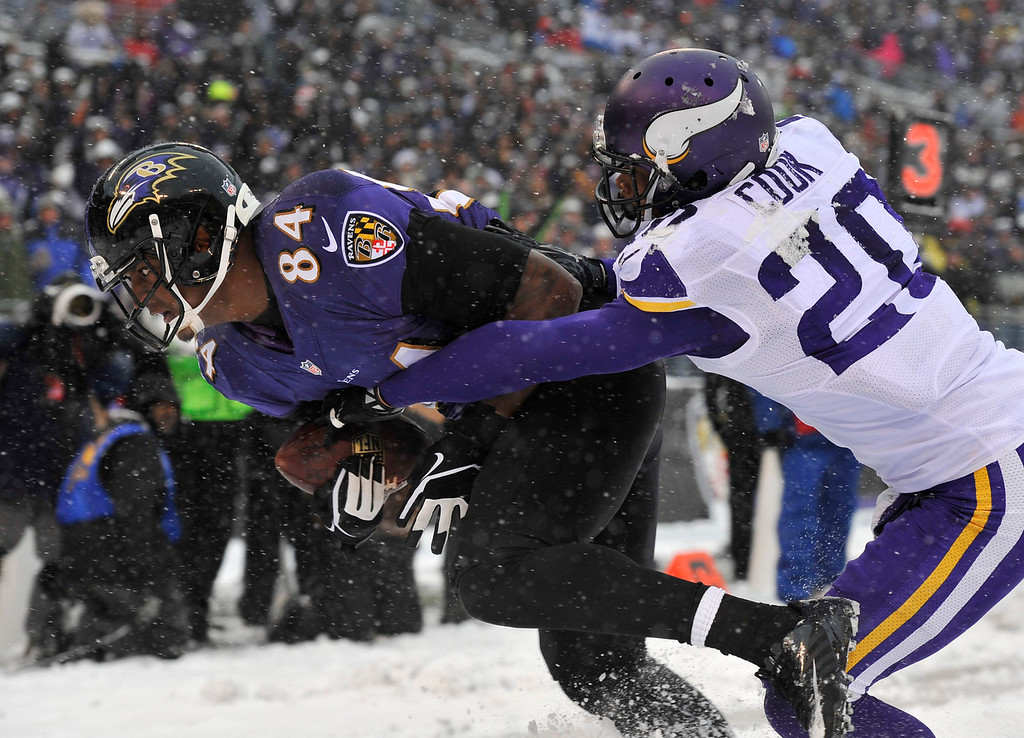 . Baltimore Ravens tight end Ed Dickson, left, scores a touchdown in front of Minnesota Vikings cornerback Chris Cook in the first half of an NFL football game, Sunday, Dec. 8, 2013, in Baltimore. (AP Photo/Gail Burton)