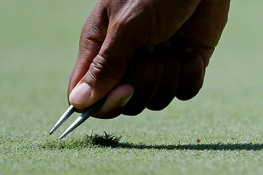 . Tiger Woods uses a ball repair tool before putting on the first green during the first round of the Quicken Loans National PGA golf tournament, Thursday, June 26, 2014, in Bethesda, Md. (AP Photo/Patrick Semansky)
