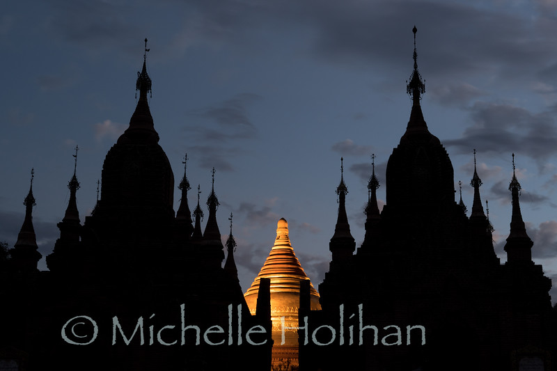 The lit up dome of Dhammayazaka Pagoda peaking out between smaller, unnamed temples at twilight in Bagan, Myanmar