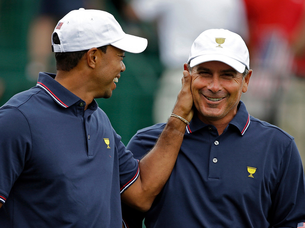 . United States\' Tiger Woods, left, pats captain Fred Couples on the face before the start of a four-ball match against the International team at the Presidents Cup golf tournament at Muirfield Village Golf Club Thursday, Oct. 3, 2013, in Dublin, Ohio. (AP Photo/Darron Cummings)