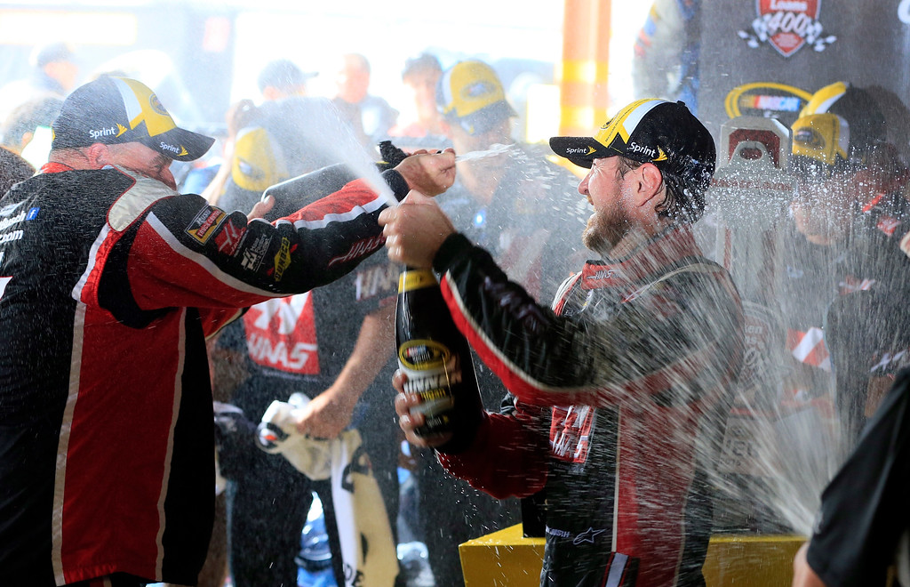. Kurt Busch sprays champagne with team members after winning the rain shortened NASCAR Sprint Cup series auto race at Michigan International Speedway, Sunday, June 14, 2015, in Brooklyn, Mich. (AP Photo/Carlos Osorio)