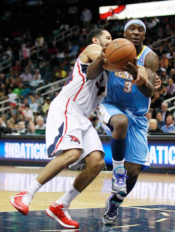 . Denver Nuggets point guard Ty Lawson (3) is fouled by Atlanta Hawks point guard Devin Harris (34) while driving to the basket during the second half of an NBA basketball game on Wednesday, Dec. 5, 2012, in Atlanta. (AP Photo/John Bazemore)