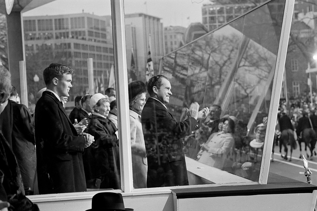 . President Nixon applauds a passing unit during the inaugural parade in Washington, D.C., Jan. 20, 1969. He stands behind bullet proof glass with his wife Pat Nixon by his side. Former First Lady Mamie Eisenhower, stands at Mrs. Nixon\'s left. (AP Photo)