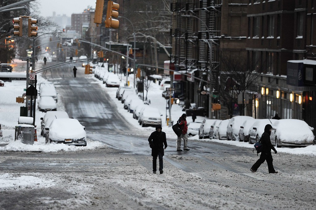 ". People walk on a deserted Lexington Avenue during what is normally a crowed morning rush hour after a snowstorm hit New York January 27, 2015. Travel bans were lifted and limited public transport resumed in New York on Tuesday as a powerful winter storm and strong winds dumped perilous snow across the northeastern United States. New York city woke up to less snow than forecast, but was eerily quiet as the National Weather Service warned of life-threatening conditions along the coast from Long Island to New England. Officials launched a vigorous defense of the blanket travel bans and rail closures, saying it had been prudent to protect lives, protect equipment and get services back to normal more quickly. ""You plan the best you can and you lead toward safety,\"" New York state Governor Andrew Cuomo told a news conference under a barrage of questioning. AFP PHOTO/Stan HONDA/AFP/Getty Images"