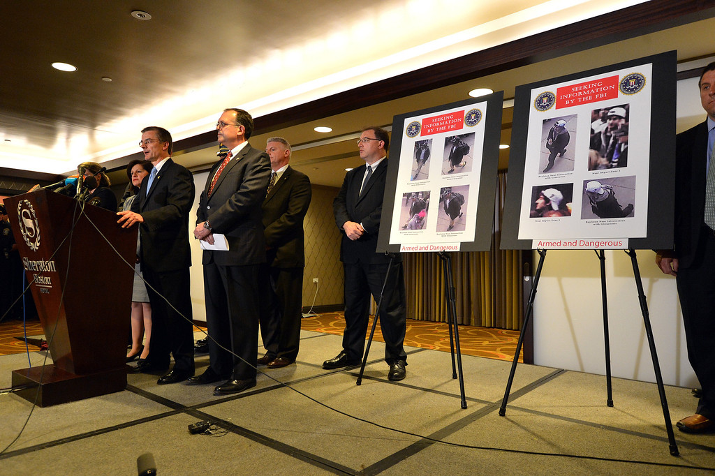 . FBI Special Agent in charge of Boston Richard DesLauriers (L, at podium) speaks at a press conference about the Boston Marathon bombings where the FBI released photographs of two suspects (R) April 18, 2013 in Boston, Massachusetts.  AFP PHOTO/Stan HONDA/AFP/Getty Images