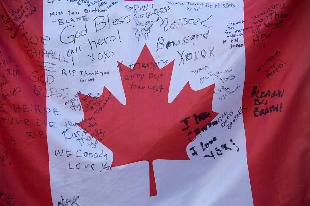 . People sign a  Canadian flag at a makeshift memorial to Cpl. Nathan Cirillo outside of The Lieutenant-Colonel John Weir Foote Armoury in Hamilton, Ontario on Thursday, Oct. 23, 2014.   (AP Photo/The Canadian Press, Peter Power)